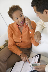Businesswoman on Cell Phone Working With Businessman on sofa