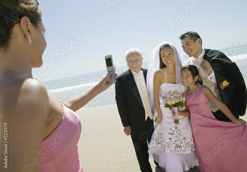 Bridesmaid photographing newly weds with family on beach