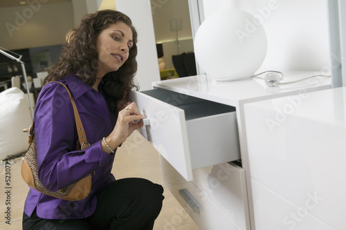 Woman Examining White Dresser drawer in furniture store, close up