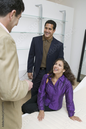 Couple Examining Mattress With Salesman in furniture store