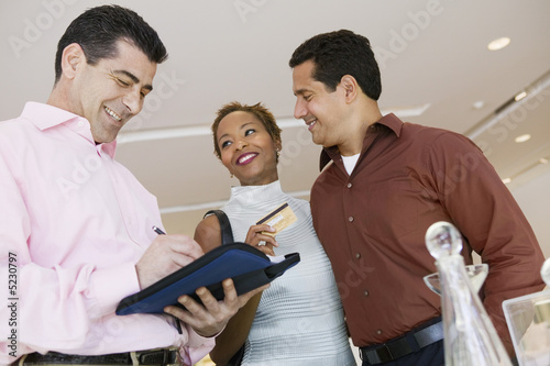 Salesman Calculating Couple's Purchase Amount