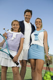 Family on Tennis Court standing by net, portrait, low angle view