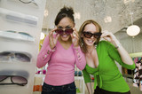 Two Girls Trying on Sunglasses in Boutique, portrait