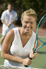 Woman standing at Tennis Net waiting for serve, portrait