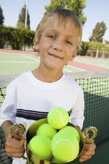 Boy on tennis court Holding Trophy Filled with tennis Balls, portrait