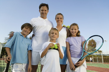 Family on Tennis Court by net, portrait, front view