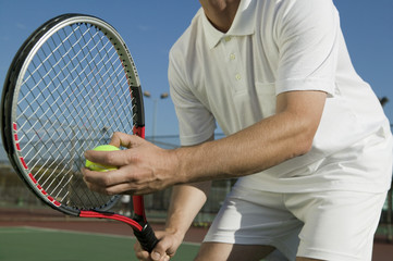 Male Tennis Player Preparing to Serve, mid section, low angle view