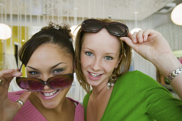 Two Girls Trying on Sunglasses in Boutique, portrait, close up