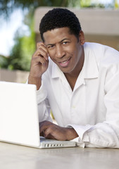Man on patio Using Laptop and talking on cell phone, portrait