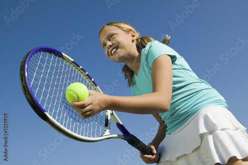 Young girl on tennis court Preparing to Serve, low angle view, close up