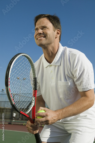 Male Tennis Player Preparing to Serve, low angle view