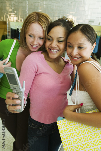 3 Girl friends Posing for Camera Phone Picture in clothing store