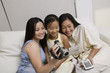 Mother and Daughters on sofa looking at Video Camera screen