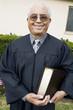 Senior Preacher in garden with Bible, portrait