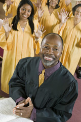 Minister at altar with Bible, gospel choir in background, portrait