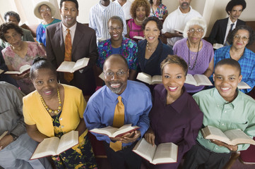 Church congregation sitting on church pews with Bible, portrait, high angle view