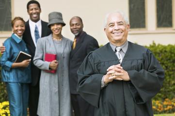 Smiling Preacher in church garden, worshipers in background, portrait