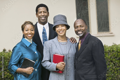 Two happy Couples in garden holding Bibles, portrait