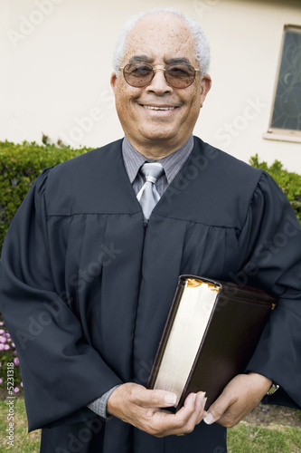 Senior Preacher in garden with Bible, portrait