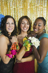 Well-dressed teenage girls showing corsages at school dance, portrait