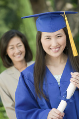 Graduate holding diploma with mother behind, outside, portrait