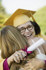Middle-aged graduate hugging daughter outside