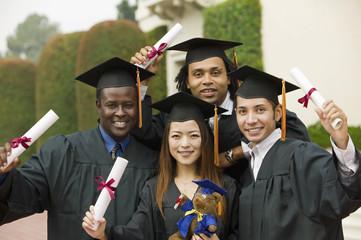 Graduates hoisting diplomas outside, portrait