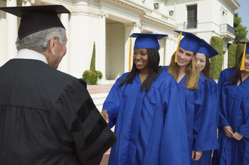 Graduates in line to shake hand of dean outside university