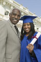 Graduate with father outside university, portrait