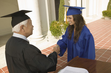 Graduate shaking hand of dean at podium outside university, elevated view