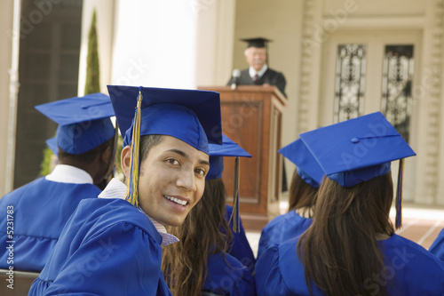 Graduates listening to speaker outside