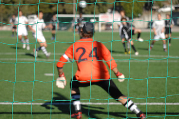 Image of a goalkeeper whatching the game, focus the net