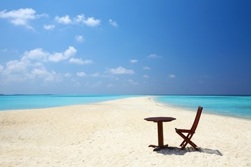 Chair and  table are on the beach