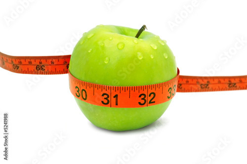 Fresh green apple with red measuring tape and water drops