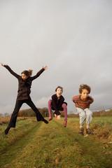 3 enfants sautant sur un chemin