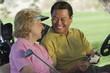 Senior couple in golf cart, smiling