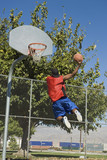 Basketball player, mid-air, shooting ball, back view