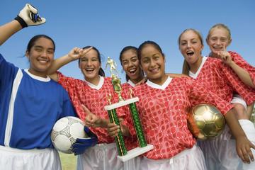 Girls' soccer team 13-17 holding trophy and celebrating, portrait