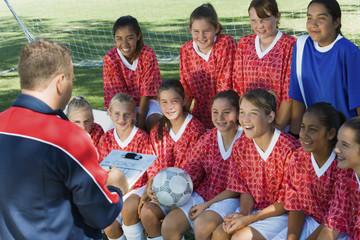 Coach talking to girls' soccer team 13-17