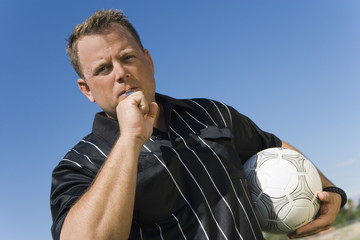 Soccer referee blowing whistle, portrait
