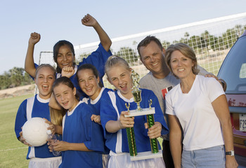 Parents with girls' soccer team 13-17 holding trophy, portrait