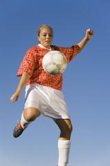 Girl 13-17 kicking soccer ball, portrait