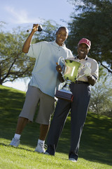 Grandfather and grandson holding golf trophy, smiling, portrait