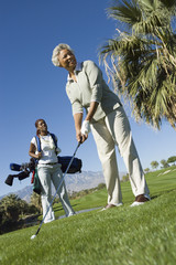 Grandmother and granddaughter on golf course, low angle view