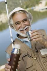 Middle-aged man fishing, holding vacuum flask, smiling, portrait
