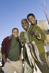 Male members of three generation family holding fishes, smiling, portrait