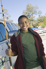 Boy holding fishing rod, smiling, portrait