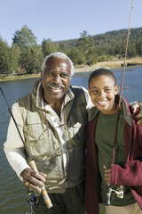 Grandfather and grandson holding fishing rods by lake, smiling, portrait