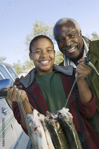 Middle-aged man with grandson holding fishes, smiling, portrait
