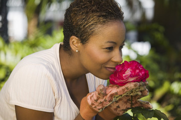 Woman smelling rose flower in garden, close-up